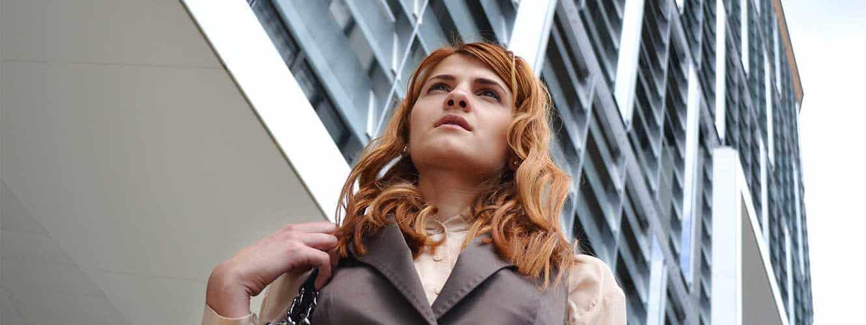 Rothaarige Dame steht vor Bürogebäude