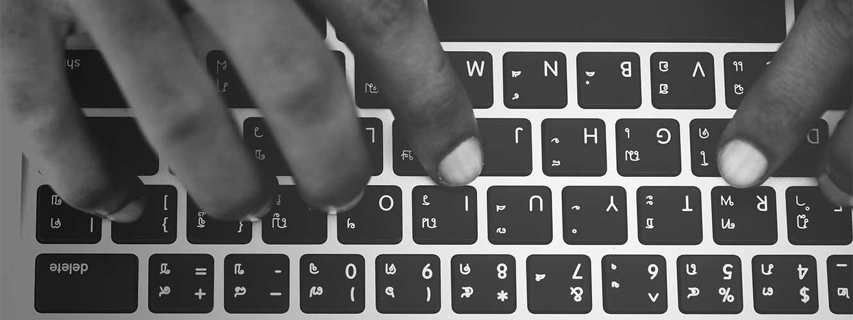 Hände über Tastatur eines MacBooks